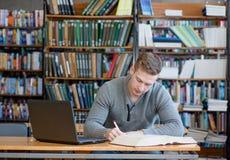 Estudiante masculino con el ordenador portátil que estudia en la biblioteca de universidad Fotografía de archivo libre de regalías