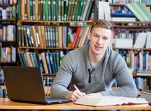 Estudiante masculino con el ordenador portátil que estudia en la biblioteca de universidad Imagen de archivo libre de regalías