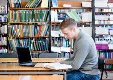 Estudiante masculino con el ordenador portátil que estudia en la biblioteca de universidad Foto de archivo