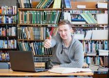Estudiante masculino con el ordenador portátil que muestra los pulgares para arriba en la biblioteca de universidad Imagen de archivo libre de regalías