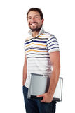 Estudiante masculino con la sonrisa de la computadora portátil Foto de archivo libre de regalías