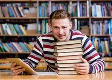 Estudiante masculino con la tableta en la biblioteca Foto de archivo