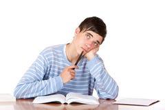 Estudiante masculino con las miradas de los libros de estudio contemplativas Foto de archivo libre de regalías