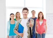 Estudiante masculino con los compañeros de clase que muestran los pulgares para arriba Fotografía de archivo libre de regalías