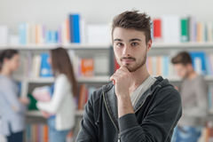 Estudiante masculino confiado que presenta en la biblioteca Imagen de archivo libre de regalías