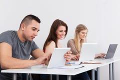 Estudiante masculino confiado que sostiene la tableta digital en el escritorio imagen de archivo libre de regalías
