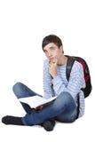 Estudiante masculino contemplativo joven que se sienta en suelo Imagenes de archivo