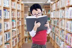 Estudiante masculino de la escuela primaria en biblioteca Fotos de archivo