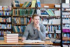 Estudiante masculino del retrato en una biblioteca Fotos de archivo libres de regalías