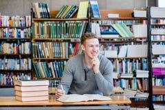 Estudiante masculino del retrato en una biblioteca Imágenes de archivo libres de regalías