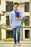 Estudiante masculino diverso sonriente With Notebooks Walking de la universidad en campus fotos de archivo