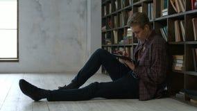 Estudiante masculino e que aprende con PC de la tableta en biblioteca almacen de video
