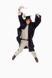 Estudiante masculino en el salto graduado del traje Imágenes de archivo libres de regalías