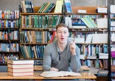 Estudiante masculino en una biblioteca que muestra el finger para arriba Imagen de archivo libre de regalías
