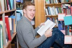 Estudiante masculino feliz con el libro que se sienta en piso en biblioteca Foto de archivo