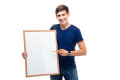 Estudiante masculino feliz que señala en tablero en blanco Fotografía de archivo libre de regalías