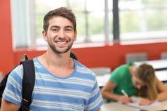 Estudiante masculino feliz que se coloca en la sala de clase Imagen de archivo libre de regalías