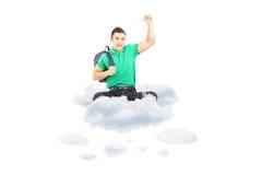 Estudiante masculino feliz que se sienta en una nube con gesticular aumentado de la mano Imagen de archivo libre de regalías