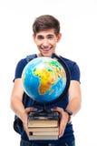 Estudiante masculino feliz que sostiene los libros y el globo Fotos de archivo