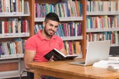 Estudiante masculino feliz Working With Laptop en biblioteca Foto de archivo libre de regalías