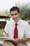 Estudiante masculino feliz Writing Notes Imágenes de archivo libres de regalías