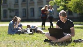 Estudiante masculino hermoso que estudia con el ordenador portátil en parque almacen de metraje de vídeo