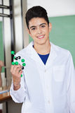 Estudiante masculino Holding Molecular Structure en laboratorio Fotografía de archivo