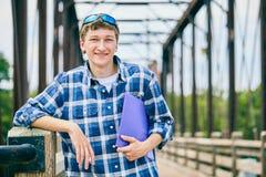 Estudiante masculino joven alegre que se coloca en el puente Fotos de archivo libres de regalías