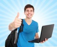 Estudiante masculino joven con el ordenador portátil que muestra el pulgar para arriba Imágenes de archivo libres de regalías