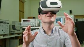 Estudiante masculino joven con los vidrios de realidad virtual en el laboratorio físico de la universidad El hombre ve el modelo  almacen de metraje de vídeo