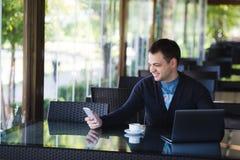 Estudiante masculino joven concentrado que se sienta y que estudia con el ordenador portátil en café Ventanas de cristal grandes  Imagen de archivo libre de regalías