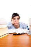 Estudiante masculino joven frustrado entre los libros de estudio Foto de archivo libre de regalías