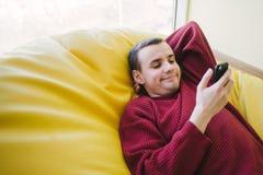 Estudiante masculino joven positivo que miente y que mira su smartphone Después de aprender en una silla cómoda Retrato interior Foto de archivo libre de regalías