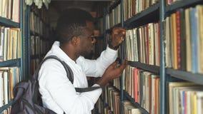 Estudiante masculino joven que elige el libro entre los estantes en la biblioteca almacen de metraje de vídeo