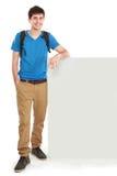 Estudiante masculino joven que lleva a cabo al tablero en blanco blanco Foto de archivo