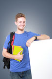 Estudiante masculino joven que lleva a cabo al tablero en blanco blanco Imagenes de archivo