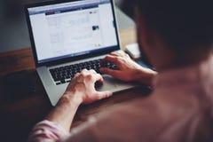 Estudiante masculino joven que manda un SMS en el ordenador que se sienta en la tabla de madera Fotos de archivo