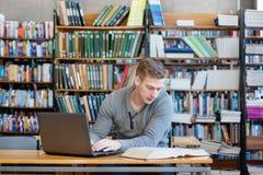 Estudiante masculino joven que mecanografía en el ordenador portátil en la biblioteca de universidad Foto de archivo libre de regalías