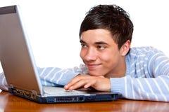 Estudiante masculino joven que pulsa y que aprende en la computadora portátil Imágenes de archivo libres de regalías