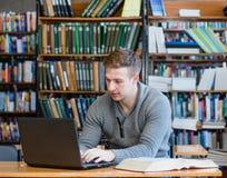 Estudiante masculino joven que usa el ordenador portátil en la biblioteca de universidad foto de archivo libre de regalías