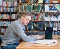 Estudiante masculino joven que usa el ordenador portátil en la biblioteca de universidad Foto de archivo