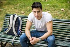 Estudiante masculino joven Sitting en banco de parque seriamente Imagen de archivo