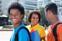 Estudiante masculino latinoamericano de risa con los amigos Foto de archivo