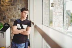 Estudiante masculino pensativo que se inclina en ventana imágenes de archivo libres de regalías