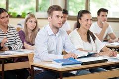 Estudiante masculino que escucha una conferencia en sala de clase Imagen de archivo