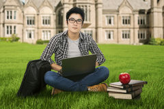 Estudiante masculino que estudia en el parque Fotografía de archivo libre de regalías