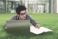 Estudiante masculino que estudia en la yarda del campus Imágenes de archivo libres de regalías