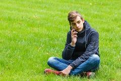 Estudiante masculino que habla en un teléfono asentado en una hierba en el parque de la ciudad Imagen de archivo libre de regalías