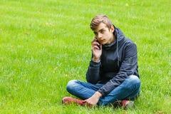 Estudiante masculino que habla en un teléfono asentado en una hierba en el parque de la ciudad Fotografía de archivo