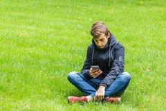 Estudiante masculino que habla en un teléfono asentado en una hierba en el parque de la ciudad Fotos de archivo libres de regalías